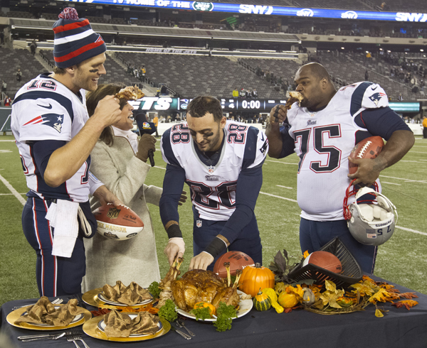 EAST RUTHERFORD, NJ - NOVEMBER 22: New England Patriots from left to right: Tom Brady, Steve Gregory, and Vince Wilfork join television broadcaster Michele Tafoya in eating turkey legs after defeating the New York Jets 49-19 at Metlife Stadium on Thursday, Nov. 22, 2012. (Photo by Matthew J. Lee/The Boston Globe via Getty Images)